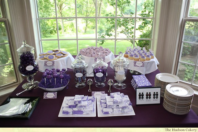 The purple and white dessert buffet includes cake pops