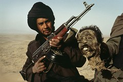 Mujahaddin holding up the head of an Afghan soldier, Kandahar, Afghanistan, 1989, by Steve McCurry