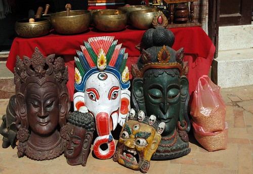 Wood carved exotic masks, diety faces, and some wrathful mask, Ganesha, metal bowls, Kathmandu, Nepal by Wonderlane