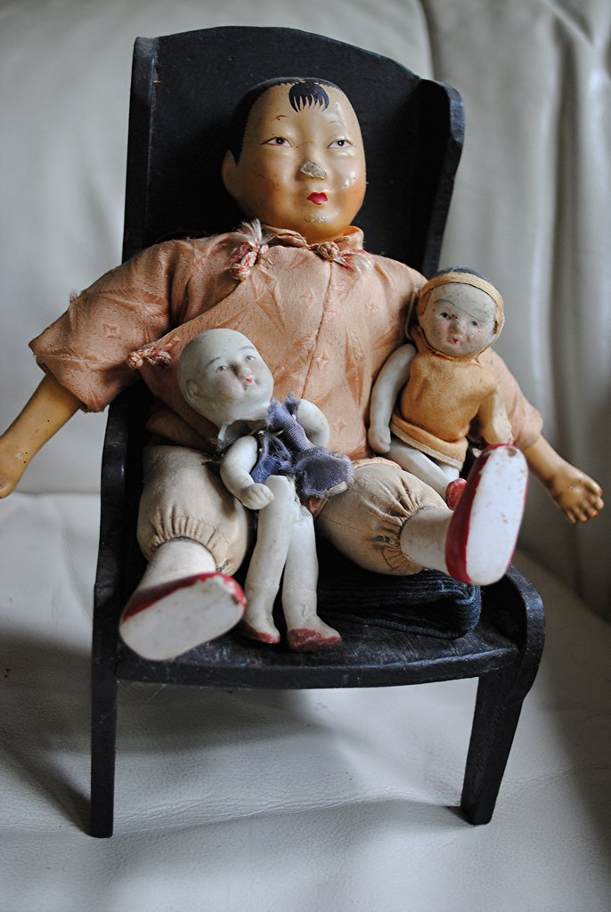 Chinese dolls sit comfortably in a black wooden chair