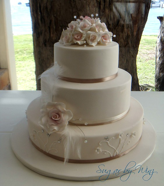 Romantic wedding cake with roses and feathers The bride wore feathers in