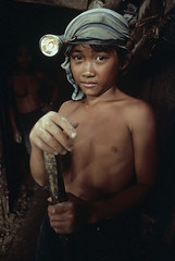 An 11-year-old boy stands outside a gold mine where he works in Mindanao, Philippines, 1985, by Steve McCurry
