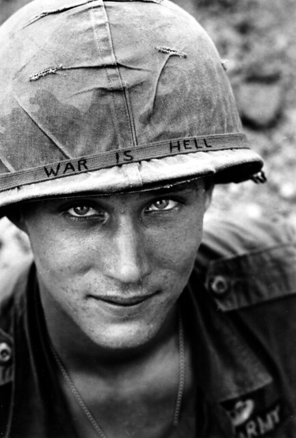 U.S. Army soldier wears a hand lettered 'War Is Hell' slogan on his helmet, in Vietnam, by Horst Faas 1965