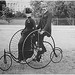 Smartly dressed couple seated on an 1886-model bicycle for two.