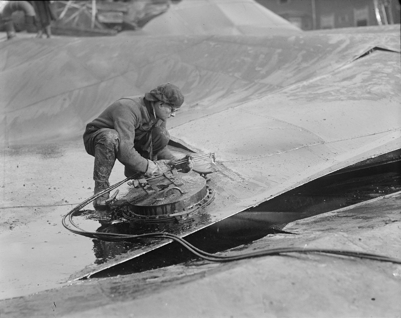 man bending over huge crumpled sheet of metal