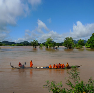 Monks on a slow boat at the Mekong River