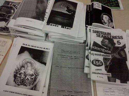a table with a smattering of zines made by people of color, including shotgun seamstress by osa atoe