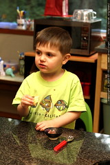 getting a lesson in eating fry bread from his mom