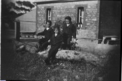 The Barabba School with three boys of the Roberts Family seated on a tree stump.