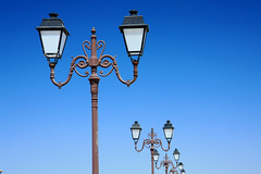 decor(0.0), signage(0.0), signaling device(0.0), street sign(0.0), tower(0.0), traffic light(0.0), light fixture(1.0), light(1.0), street light(1.0), electricity(1.0), blue(1.0), sky(1.0), lighting(1.0),
