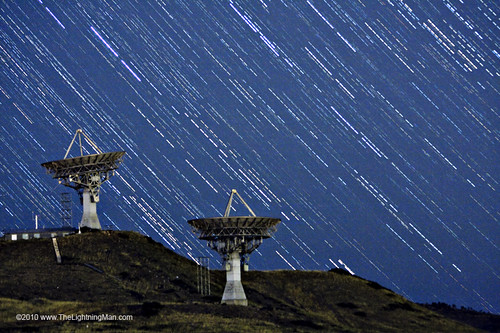 Long exposure layered image of Stars buzzing by two Satellite Communication Antennas to the sky, photo Striking Photography by Bo