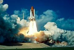 tower(0.0), cloud(1.0), rocket(1.0), space shuttle(1.0), spacecraft(1.0), vehicle(1.0), space(1.0), blue(1.0), sky(1.0),