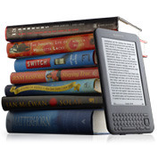Stack of books next to a Kindle