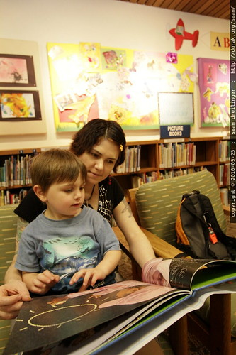 in the children's library, reading a story in mom's lap