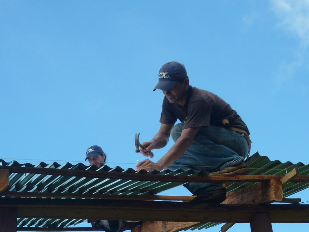 Panthera Field Technician, Ever Urbina, is shown securing the aluminum sheet to the wooden beam to form the roof of the enclosure.   Read 'Panthera's Guide to Building a Livestock Corral' from our October 2010 newsletter at www.panthera.org/november-2010-newsletter.  Learn more about the work Panthera's Costa Rica team is doing at pantheracostarica.org/.   Also read about our jaguar conservation work in other countries through our Jaguar Corridor Initiative - www.panthera.org/programs/jaguar/jaguar-corridor-initiative - and Pantanal Jaguar Project - www.panthera.org/programs/jaguar/pantanal-jaguar-project.    © Josephine Dusapin