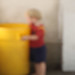 Child in Red by Yellow Container