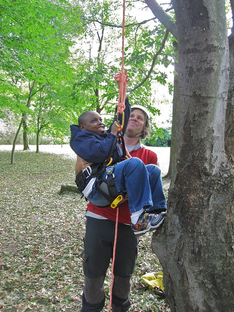 Chris Roddick gives a young Green Horizon student a boost as he learns the basics of tree climbing.