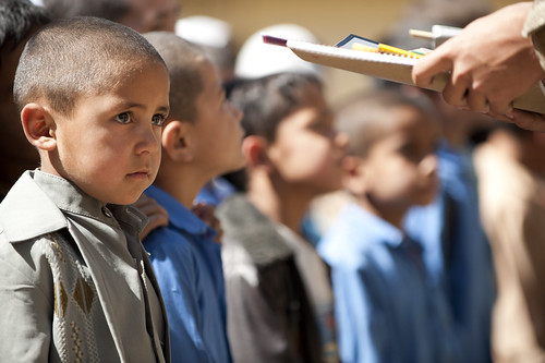 An Afghan school boy waits for his new school supplies