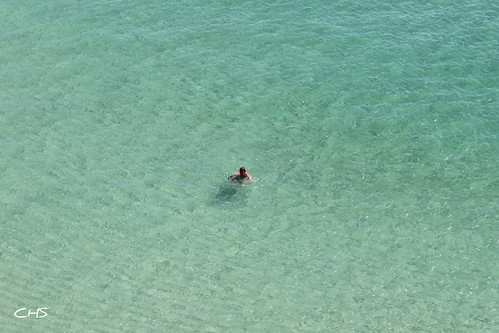 Carribbean? Nah, Cornwall at it's finest!  A lone swimmer swims the crystal blue waters off Porthcurno beach, West Cornwall by Stocker Images