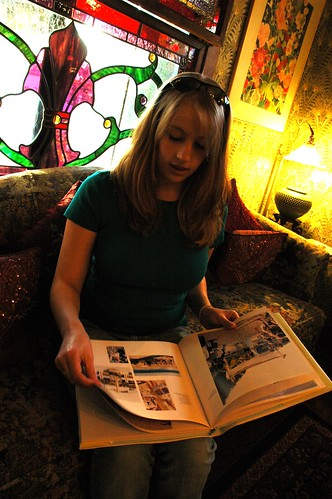 Jessie Rabbit reading a book, under a large stained glass window, in the unique and charming Mill Rose Inn, Half Moon Bay, California, USA
