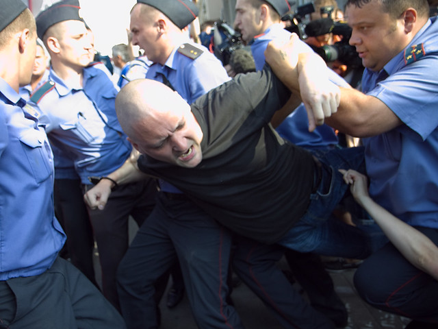 Russian policemen detain Sergei Udaltsov during a protest rally in central Moscow