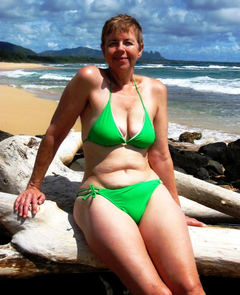 Old lady in bikini on beach