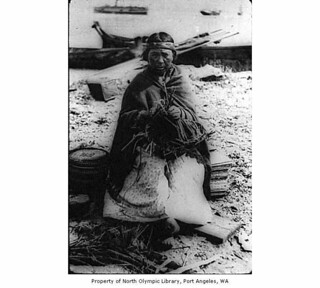 Makah woman weaving a basket on the beach at Neah Bay
