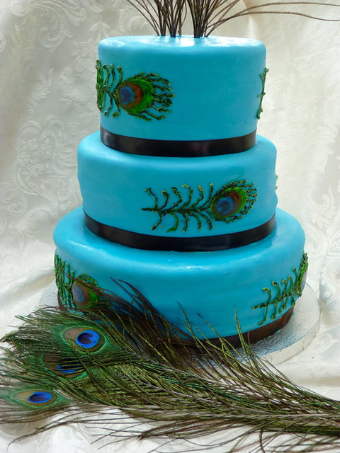 Peacock themed wedding cake covered in fondant and hand painted peacock