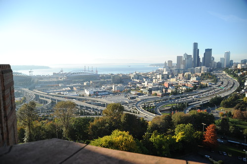 Edge of the art deco style building exterior, the port of Seattle, city skyline, freewalks, trees, blue sky, fall, Washington, USA by Wonderlane