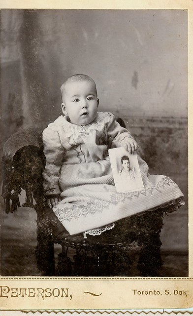 A baby holds a photo of his mother cabinet photo
