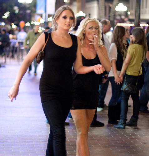 Two blonde girls smoking while walking through the Gaslamp
