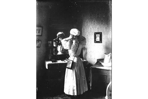 Unidentified woman trying on hat in front of mirror, Washington