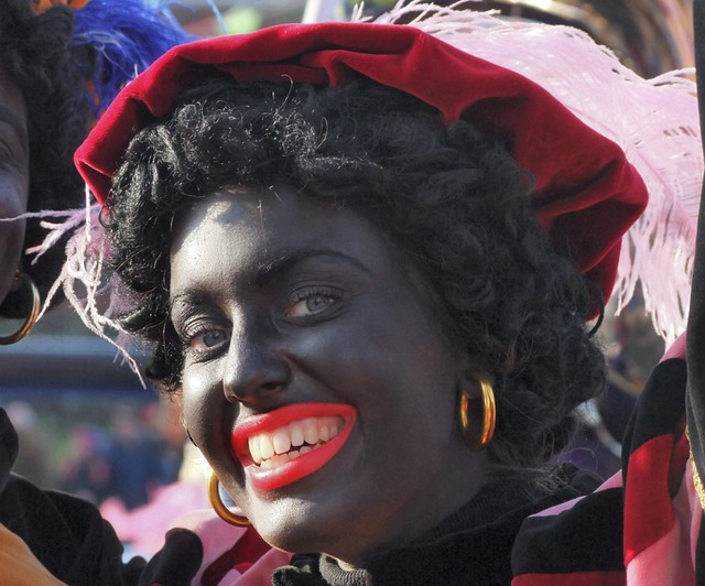 A person dressed in blackface with a medieval outfit, representing black pete