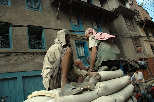 Two Nepalese men riding the bags, on a tractor to market, streets of Kathmandu, Nepal by Wonderlane
