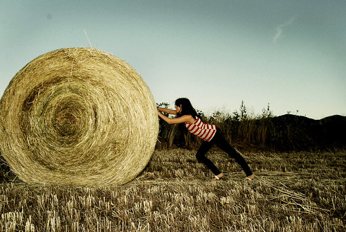 Color photograph of a woman pushing a gigantic hay roll