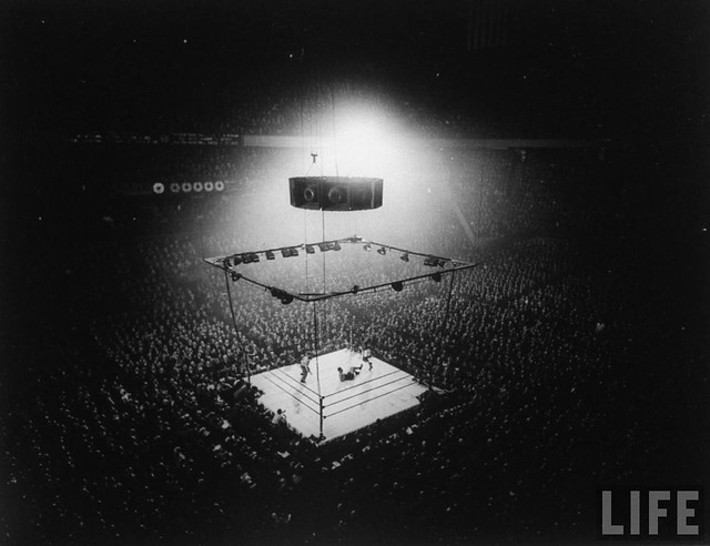 Spectators and boxing ring as heavyweight champion Joe Louis lies on canvas after being knocked down by 'Jersey' Joe Walcott, by Gjon Mili 1947
