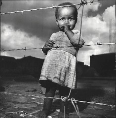 Three-yr-old native girl standing at barbed-wire fence that marks the boundary of her home, Maroka, South Africa, by Margaret Bourke-White 1950