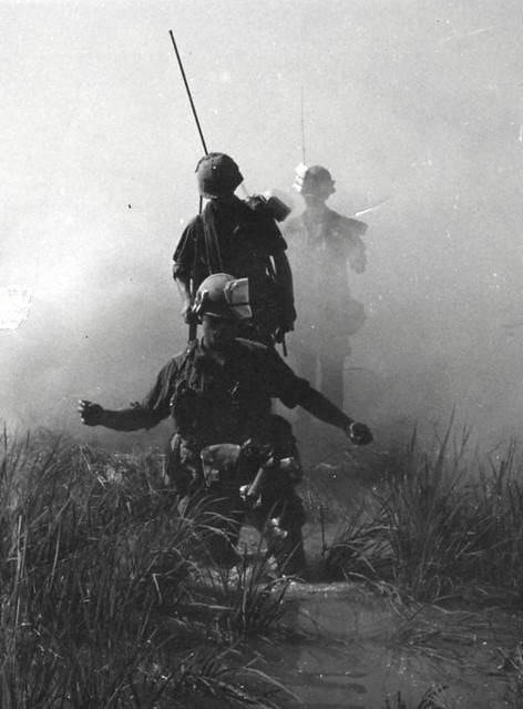 Out of the mist, U.S. Army troops move through a rice paddy south of Saigon, Vietnam