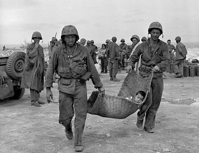 American Marines carrying a wounded child to an aid station after the invasion of Saipan, by Peter Stackpole 1944