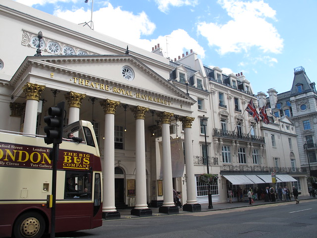 Theatre Royal Haymarket in London with blue sky with big bus in front