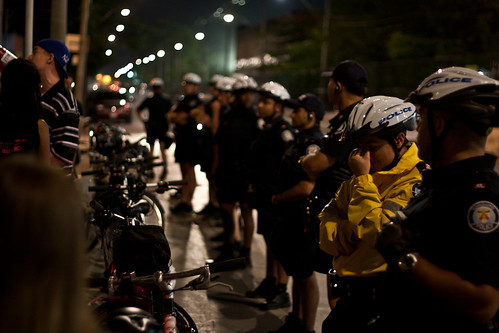 Police lined up along the road facing protesters