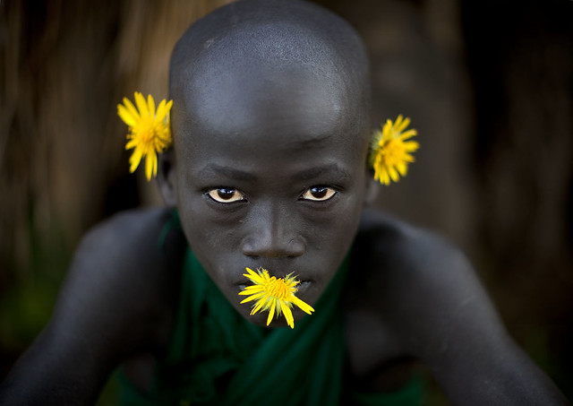 Surma boy with yellow flowers - Tulgit Omo Ethiopia - Tribes of the World