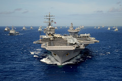 In this file photo, the aircraft carrier USS Ronald Reagan (CVN 76) leads a group of international ships in formation during Rim of the Pacific (RIMPAC) 2010. (U.S. Navy photo by Mass Communication Specialist 1st Class Scott Taylor)