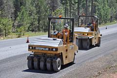 forklift truck(0.0), asphalt(1.0), vehicle(1.0), transport(1.0), road(1.0), construction equipment(1.0),
