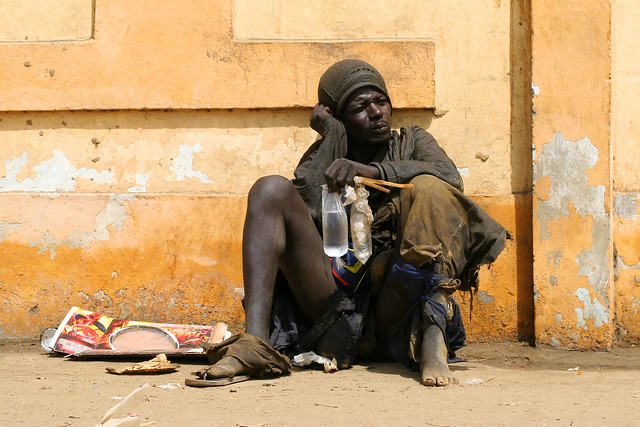 A hopeless man sitting in the streets of Dakar, Senegal.