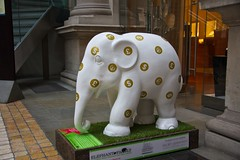 statue from London Elephant Parade, white baby elephant with gold currency symbol spots