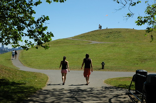 Two people walking onto the post industrial Gasworks park, clear and sunny, with a kite flying, Seattle, Washington, USA