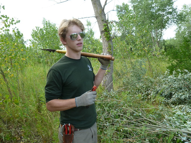 A volunteer shows off tools of the day: lopers, shears, folding saw. Photo by Elizabeth Peters.