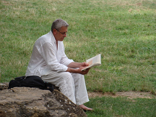 Man reading with barefoot in the grass