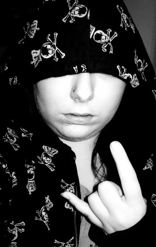 A girl wearing a black hoodie with white skulls on it.
